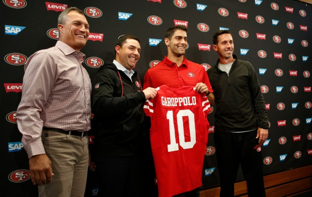 New 49ers quarterback Jimmy Garoppolo holds his new jersey as he poses for a photo with, from left, 49ers general manager John Lynch, owner Jed York and head coach Kyle Shanahan in the Levi's Stadium auditorium in Santa Clara, California, Tuesday, Oct. 29, 2017. (Patrick Tehan/Bay Area News Group)