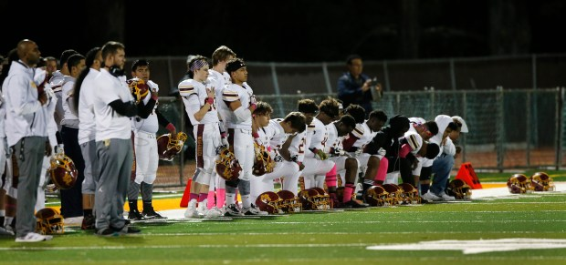 A group of Menlo-Atherton players take a knee during the national anthem at Half Moon Bay High School on Friday, Oct. 20, 2017, in Half Moon Bay, Calif. (Jim Gensheimer/Bay Area News Group)