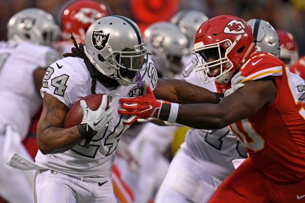 Oakland Raiders' Marshawn Lynch (24) runs with the ball while being tackled by Kansas City Chiefs' Justin Houston (50) in the first quarter of their NFL game at the Coliseum in Oakland, Calif. on Thursday, Oct. 19, 2017. (Jose Carlos Fajardo/Bay Area News Group)