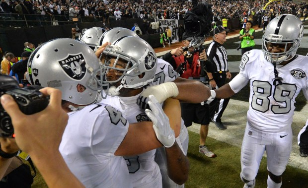 Oakland Raiders quarterback Derek Carr (4), left, and Michael Crabtree (15) celebrate after Crabtree caught Carr's pass, tying their NFL game against the Kansas City Chiefs at the Coliseum in Oakland, Calif. on Thursday, Oct. 19, 2017. The Raiders went on to win the game 30-31. (Doug Duran/Bay Area News Group)