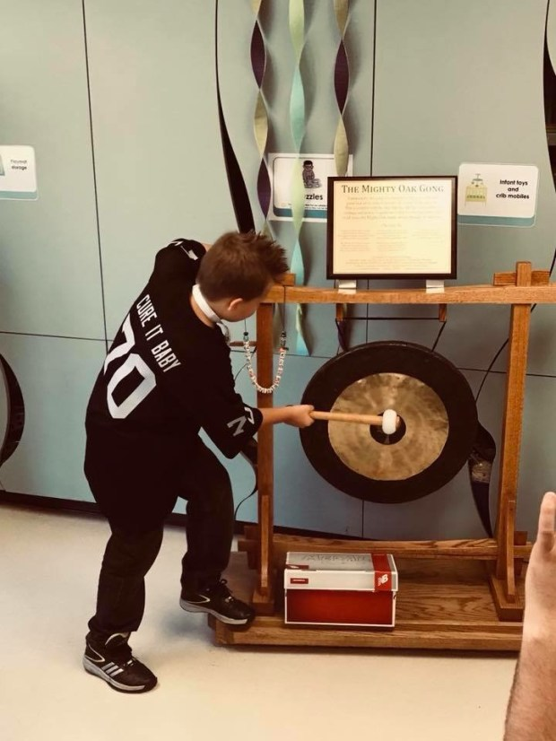 Chase bangs a gong to signify the end of his chemotherapy two weeks ago. (Courtesy of Jason DeLisle)