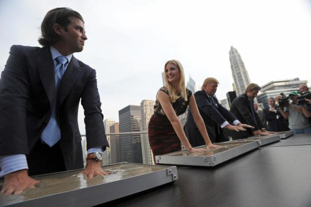 Real estate developer Donald Trump (2nd-R) and his children (L-R) Donald, Jr., Ivanka and Eric make hand prints during during a press conference at the Trump International Hotel and Tower in Chicago on September 24, 2008. Trump's 1,360-foot (414.5-meter), 92-story tower is expected to be finished in six months and will stand as the second-tallest building in Chicago, after the Sears Tower. AFP PHOTO/Amanda Rivkin (Photo credit should read Amanda Rivkin/AFP/Getty Images)