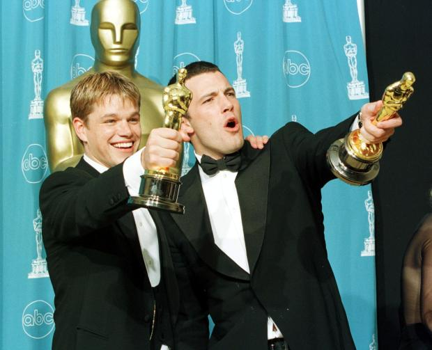 """Oscar winners Matt Damon (L) and Ben Affleck hold the awards they won for best original screenplay for the film """"Good Will Hunting"""" a 1997 executive produced by then-MIramax chief Harvey Weinstein. (Photo credit should read HAL GARB/AFP/)"""