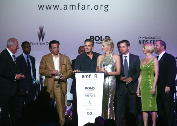 "Mougins, FRANCE: US actor and producer George Clooney (C, L) talks 23 may 2007 surrounded by US actors Andy Garcia (3rdL), Sharon Stone (C, R), Matt Damon (3rdR), Ellen Barkin (2ndR) and US producer Harvey Weinstein (R) during auction at the amfAR?s annual ""Cinema Against AIDS 2007"" (American Foundation for AIDS Research) event at Le Moulin de Mougins during the 60th edition of the International Cannes Film Festival in Mougins, southern France. amfAR, The Foundation for AIDS Research, is one of the world's leading nonprofit organizations dedicated to the support of AIDS research, HIV prevention, treatment education, and the advocacy of sound AIDS-related public policy. AFP PHOTO / FRED DUFOUR (Photo credit should read FRED DUFOUR/AFP/Getty Images)"