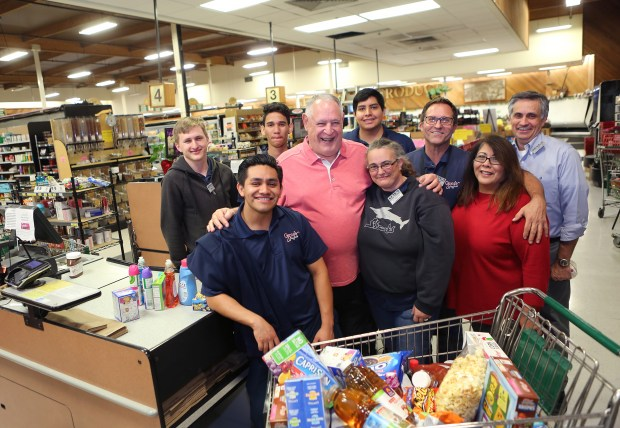 Dick Giomi owner of Gene's Market in Saratoga, takes a picture with some of his long time employees: Evan Riley, left, Manuel Cadena, Hodeierz Gonzalez, Michael Vazquez, Elizabeth Hassler, Duane Chapman, Delicia Moghadan and Ian Hunter during a recent visit to the store. The market will be closing for good after 47 years in Saratoga on Oct. 15. (George Sakkestad/Staff Photographer)