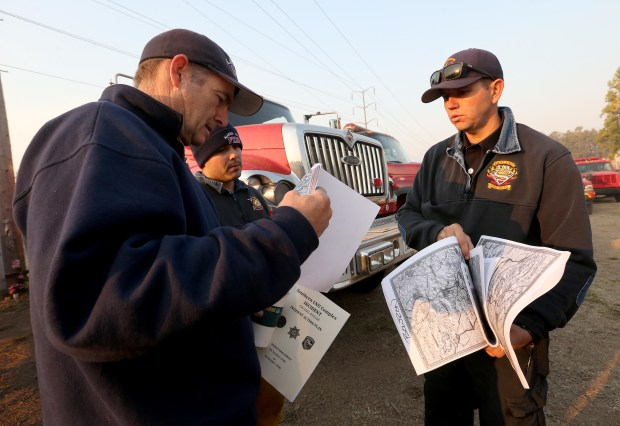 Oakland Battalion Chief James Bowron, right, and firefighter Mike Berry go over maps at the Napa Valley Fairgrounds staging area in Napa, Calif., on Thursday, Oct. 12, 2017. A strike team comprised of Oakland, Alameda County, Fremont and Hayward firefighters has been there since early Monday morning when the Wine Country fires began. (Jane Tyska/Bay Area News Group)
