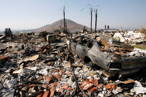 The garaged BMW vehicle of resident David Crane is seen in the remains of their home in the Rancho Bernardo area of San Diego, Calif. Friday, Oct. 26, 2007, after the Witch fire destroyed it earlier in the week.(AP Photo/Damian Dovarganes)