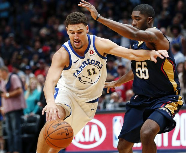 Golden State Warriors guard Klay Thompson (11) drives against New Orleans Pelicans guard E'Twaun Moore (55) in the first half of an NBA basketball game in New Orleans, Friday, Oct. 20, 2017. (AP Photo/Gerald Herbert)