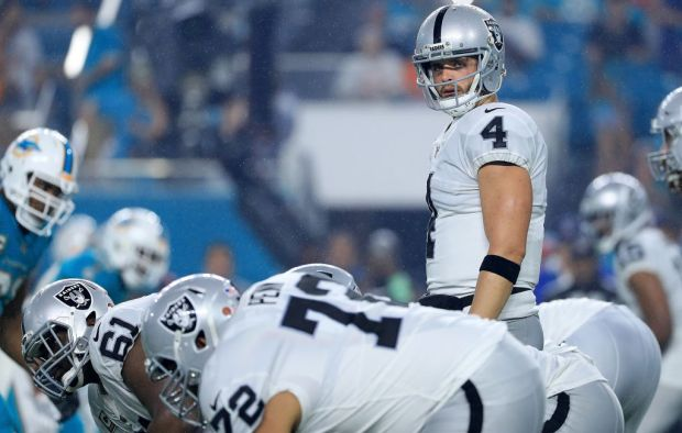 Derek Carr calls a play against the Miami Dolphins. (Photo by Mike Ehrmann/Getty Images)