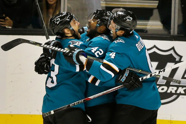 San Jose Sharks right wing Joel Ward (42), center, is embraced by teammates, Barclay Goodrow (23) and Brenden Dillon (4) after he scored in the third period of their NHL game at SAP Center in San Jose, Calif., on Saturday, Nov. 4, 2017. The Sharks won 2-1. (Patrick Tehan/Bay Area News Group)