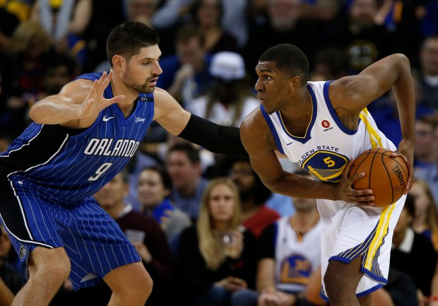 Golden State Warriors' Kevon Looney (5) controls the ball against Orlando Magic's Nikola Vucevic (9) in the third quarter at Oracle Arena in Oakland, Calif. on Monday, Nov. 13, 2017. (Nhat V. Meyer/Bay Area News Group)