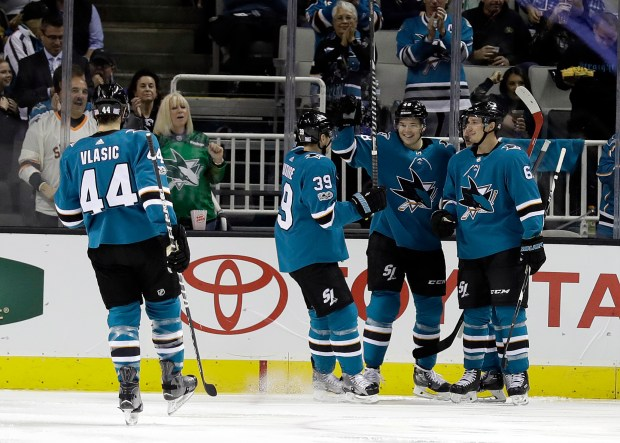 San Jose Sharks' Tomas Hertl, center, is hugged by teammates after scoring against the Vancouver Canucks during the first period of an NHL hockey game Saturday, Nov. 11, 2017, in San Jose, Calif. (AP Photo/Marcio Jose Sanchez)
