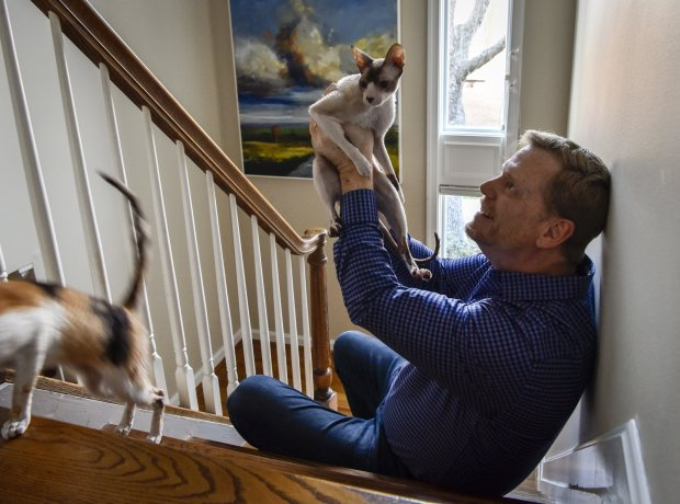Mark King, whose HIV positive status is now considered non transferrablewith proper treatment, at home with Henry, the cat, in Baltimore. MUST CREDIT: Washington Post photo by Bill O'Leary