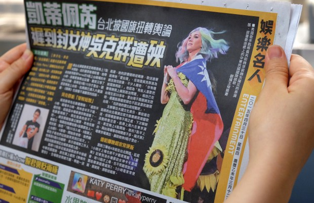 "In this photo illustration taken on April 30, 2015, a local resident reads a newspaper showing US singer Katy Perry wearing Taiwan's national flag in Taipei. The intricacies of the ""one China"" policy may not have been uppermost on her mind, but US pop star Katy Perry caused a stir in Asia this week with her politically-charged choice of dress at a Taipei concert. AFP PHOTO / Sam Yeh (Photo credit should read SAM YEH/AFP/Getty Images)"