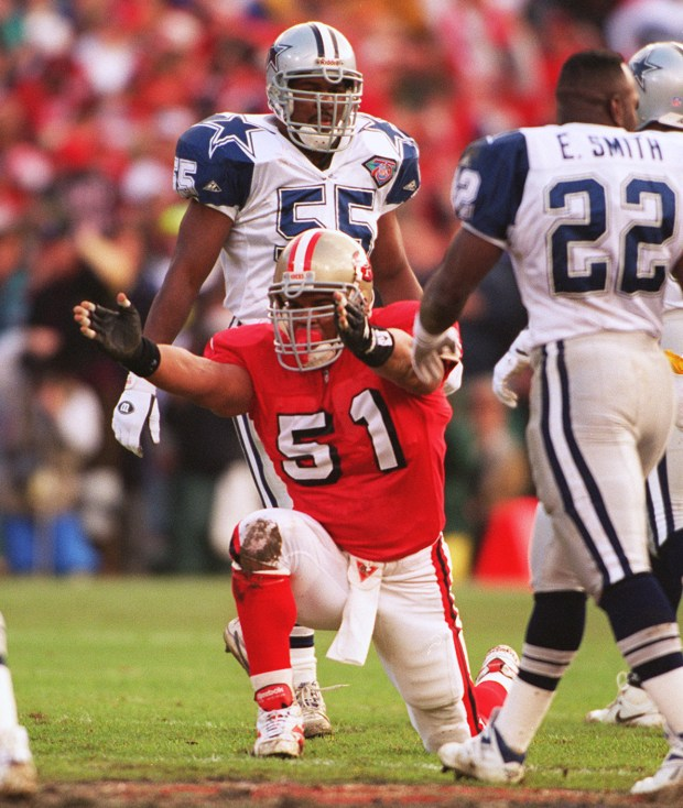 PHOTO BY PATRICK TEHAN The 49ers' Ken Norton Jr. signals after a fumble recovery in the first half as Cowboys' #55 Robert Jones and Emmitt Smith look on.