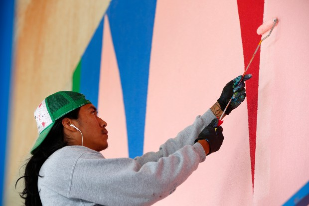 Artist, Jacque Fragua, works on a new mural in the entryway of the Children's Discovery Museum in San Jose, California, on Tuesday, Nov. 28, 2017. The huge mural is part of a pilot program by the museum to celebrate creativity and community building. (Gary Reyes/ Bay Area News Group)