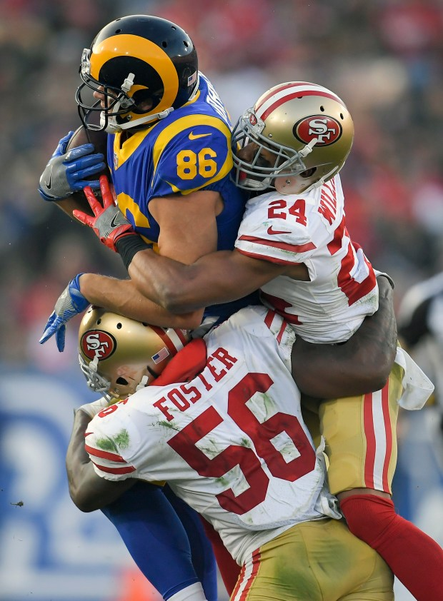 Los Angeles Rams tight end Derek Carrier, top, is tackled by San Francisco 49ers outside linebacker Reuben Foster and defensive back K'Waun Williams (24) during the second half of an NFL football game Sunday, Dec. 31, 2017, in Los Angeles. (AP Photo/Mark J. Terrill)