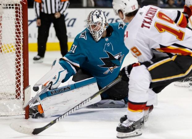 San Jose Sharks goaltender Martin Jones (31) blocks a shot against Calgary Flames' Matthew Tkachuk (19) in the overtime period at the SAP Center in San Jose, Calif., on Thursday, Dec. 28, 2017. (Nhat V. Meyer/Bay Area News Group)