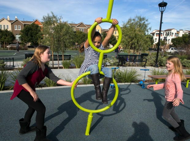 From left, Ryley Palone, 9, Addie Ruelli, 6, and Ava Palone 7, play in the playground during the unveiling of Elaine Richardson Park in San Jose, California on Saturday, December 9, 2017. The Palone's are great great grandchildren of Elaine Richardson. (LiPo Ching/Bay Area News Group)