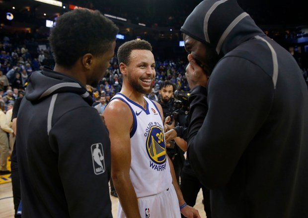 Golden State Warriors' Stephen Curry (30) laughs with Denver Nuggets players after the Warriors 124-114 NBA win at Oracle Arena in Oakland, Calif., on Monday, Jan. 8, 2018. (Jane Tyska/Bay Area News Group)