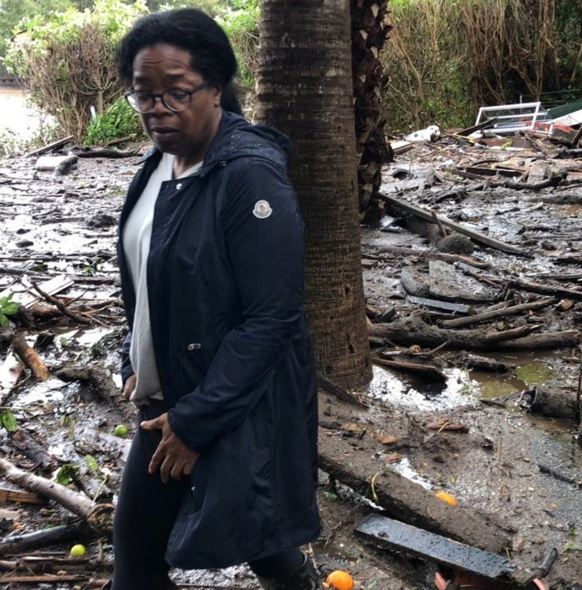 Winfrey shows Winfrey standing in debris and mud flow as she looks at her neighbors property in Montecito Calif. As search dogs clambered on heaps of wood that used to be homes mud-spattered rescue