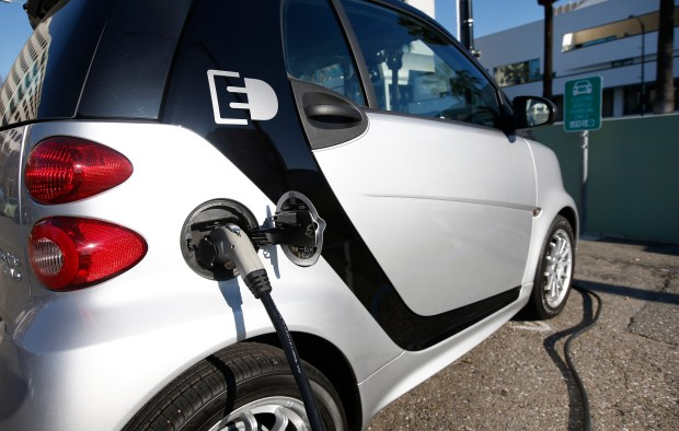 An electric Smart car is plugged in at an electric vehicle charging station in downtown San Jose, Calif., on Friday, Jan. 23, 2015. (Gary Reyes/Bay Area News Group)