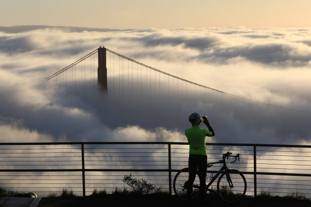 A cyclist atop the Marin headlands takes in the view as the north tower of the Golden Gate Bridge peaks through the morning fog Friday, Jan. 13, 2018. (Karl Mondon/Bay Area News Group)
