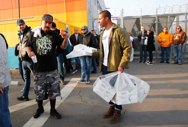 John Gonzales, left, of San Jose, gets a free donut from Marc Lejay, right, while waiting in line at the opening of the Caliva cannabis dispensary in San Jose on Monday, Jan. 1, 2018. New Year's Day marks the first day dispensaries in California will be legally allowed to sell recreational cannabis through retail stores. (Gary Reyes/ Bay Area News Group)