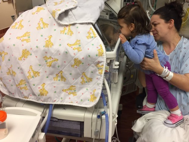 Big sister Avery, 19 months, peers into the incubator holding one of herbaby siblings at Kaiser Walnut Creek on Friday morning. Amy Kempel, her mother, successfully delivered quintuplets on Thursday evening at the hospital after 27 weeks of pregnancy. (Courtesy of Chad Kempel)