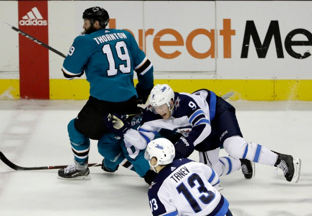San Jose Sharks center Joe Thornton, left, collides with teammate Mikkel Boedker, center, and Winnipeg Jets' Andrew Copp, right, during the third period of an NHL hockey game Tuesday, Jan. 23, 2018, in San Jose, Calif. (AP Photo/Marcio Jose Sanchez)