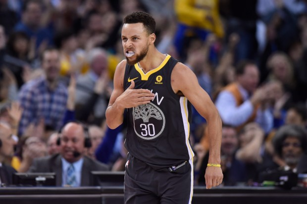 Golden State Warriors' Stephen Curry (30) reacts after scoring a 3-point basket against the Boston Celtics during the first quarter of their NBA game at the Oracle Arena in Oakland, Calif. on Saturday, Jan. 27, 2018. (Jose Carlos Fajardo/Bay Area News Group)