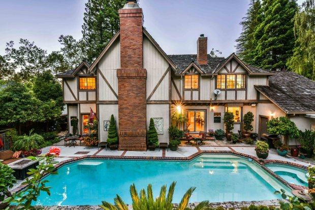 The Tudor-style home comes with lush gardens and an inviting pool area perfect for entertaining.