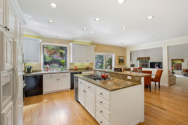 The home's updated kitchen is an open plan with casual dining space, granite counters and a breakfast bar.
