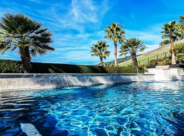 A solar-heated swimming pool with waterfall features and adjacent spa are wrapped in a paver patio.