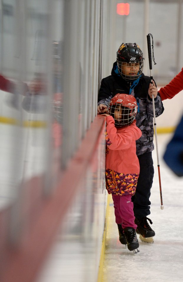 Anderson Ayala, 15, of Boonsboro, Md., who is visually impaired and LeslieSaenz, 5, who is sighted, try ice skating for the first time at an open-ice day at Kettler Capital's Iceplex. MUST CREDIT: Photo for The Washington Post by Essdras M Suarez