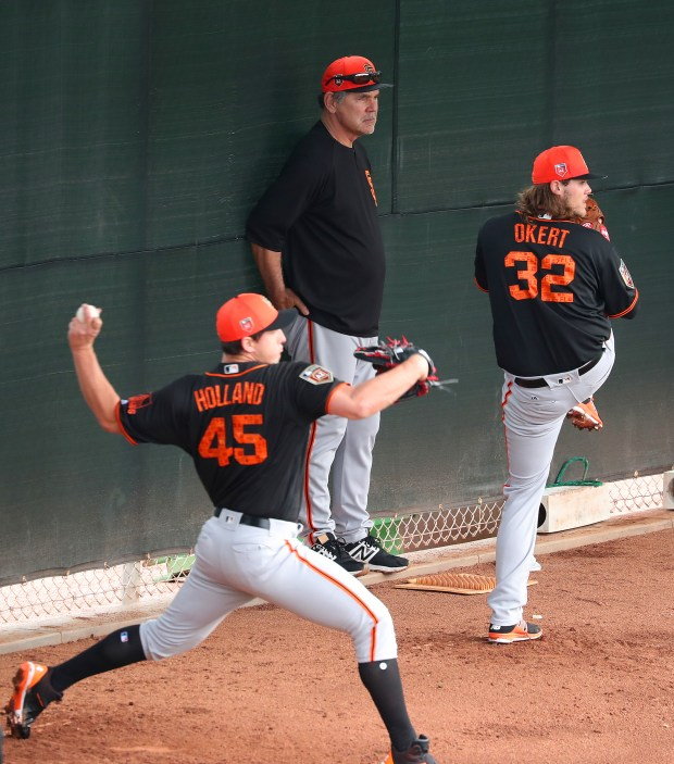 San Francisco Giants manager Bruce Bochy, center, watches pitchers Derek Holland, left, and Steven Okert, right, throw at Scottsdale Stadium during Spring Training workouts on Thursday, Feb. 15, 2018, in Scottsdale, Ariz. (Aric Crabb/Bay Area News Group)