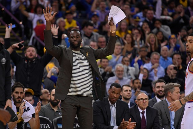Golden State Warriors' Draymond Green (23) gestures after a dunk by teammate Golden State Warriors' Andre Iguodala (9) during the third quarter of their NBA game at the Oracle Arena in Oakland, Calif., on Monday, Feb. 12, 2018. Green is on the bench with an injury to his left hand. (Jose Carlos Fajardo/Bay Area News Group)