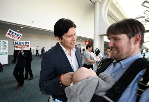 U.S. Senate candidate, California State Senator Kevin de León, D- Los Angeles, center, talks with a supporter at the 2018 California Democrats State Convention Saturday, Feb. 24, 2018, in San Diego. (AP Photo/Denis Poroy)