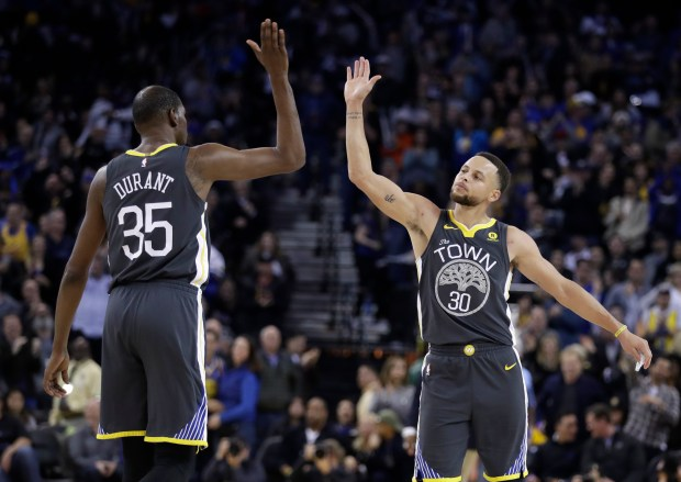 Golden State Warriors' Kevin Durant, left, celebrates after a basket by teammate Stephen Curry, right, during the second half of an NBA basketball game against the Los Angeles Clippers on Thursday, Feb. 22, 2018, in Oakland, Calif. (AP Photo/Marcio Jose Sanchez)