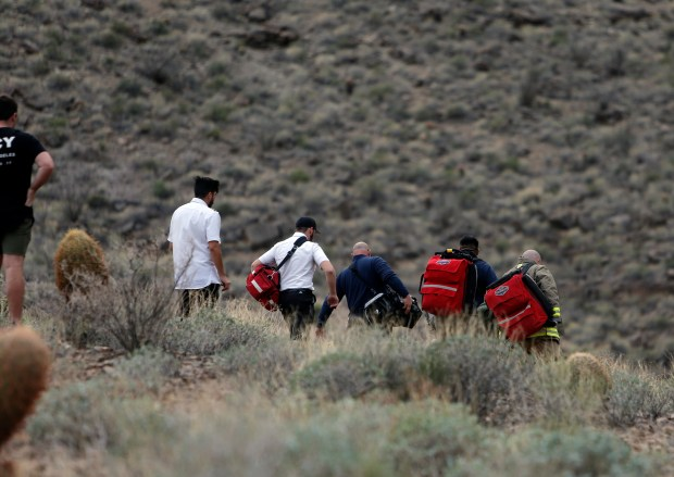 In this Saturday, Feb. 10, 2018, photo, emergency personnel arrive at the scene of a deadly tour helicopter crash along the jagged rocks of the Grand Canyon, in Arizona. (Teddy Fujimoto via AP)