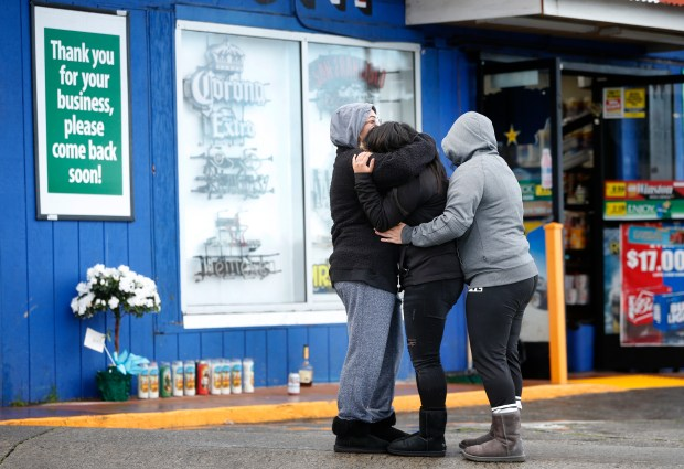 People grieve outside the Hillside Market in unincorporated Daly City, Calif., Monday morning, Feb. 26, 2018, in the wake of a double homicide that occurred there last night. Broadmoor police are investigating. (Karl Mondon/Bay Area News Group)