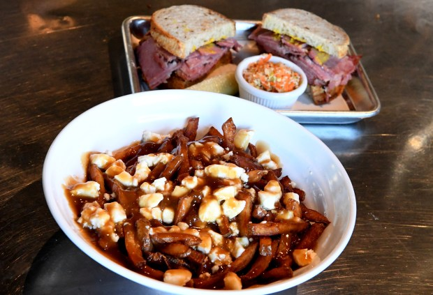 Georgie's Classic Quebec Poutine, made with triple fried red potato fries, fresh cheese curds, and brown gravy, is photographed next to a Montreal smoke meat sandwich at Augie's Montreal Deli in Berkeley, Calif., on Tuesday, Feb. 13, 2018. The Bay Area's first Canadian deli, offers what is known as Montreal smoke meat, a cross between pastrami and corned beef. (Doug Duran/Bay Area News Group)