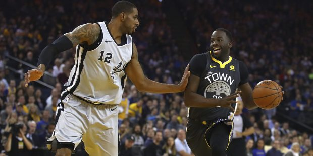 Golden State Warriors' Draymond Green, right, drives the ball against San Antonio Spurs' LaMarcus Aldridge (12) during the first half of an NBA basketball game Saturday, Feb. 10, 2018, in Oakland, Calif. (AP Photo/Ben Margot)
