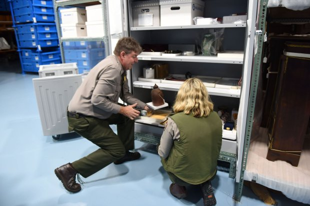 Mike Litterst, a spokesman for the National Mall and Memorial Parks, andcurator Laura Anderson remove containers left at the Vietnam Veterans Memorial from a cabinet at the National Park Service archive in Landover, Md. MUST CREDIT: Washington Post photo by Michael Robinson Chavez
