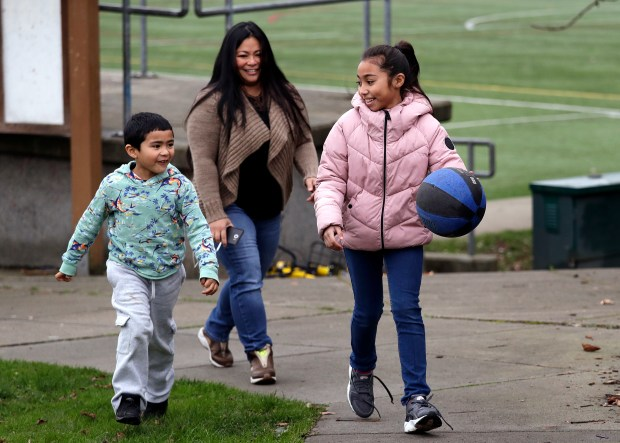 In this Thursday, Feb. 15, 2018, photo, Lara Mae Chollette, a coach of youth soccer and basketball, follows her daughter Linda, 10, right, and son Jaylen, 7, at a playground in Seattle. Horrific cases and allegations of predatory crimes against youth in gymnastics, swimming and football, among other sports, have jolted many parents who say they believe sports can be an important part of their child's development. Some now feel compelled to take a more cautious approach in monitoring adult interactions, as advancement beyond pee-wee leagues become increasingly coach-driven. (AP Photo/Elaine Thompson)