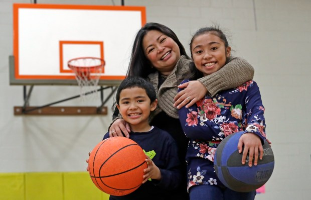 In this Thursday, Feb. 15, 2018, photo, Lara Mae Chollette, a coach of youth soccer and basketball, poses for a photo with her son Jaylen, 7, left, and daughter Linda, 10, at a community gym in Seattle. Horrific cases and allegations of predatory crimes against youth in gymnastics, swimming and football, among other sports, have jolted many parents who say they believe sports can be an important part of their child's development. Some now feel compelled to take a more cautious approach in monitoring adult interactions, as advancement beyond pee-wee leagues become increasingly coach-driven. (AP Photo/Elaine Thompson)