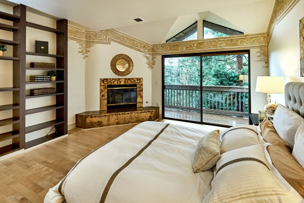 The master bedroom features stylish detailing, a cozy fireplace and sliding glass doors that lead to a private Trex deck.
