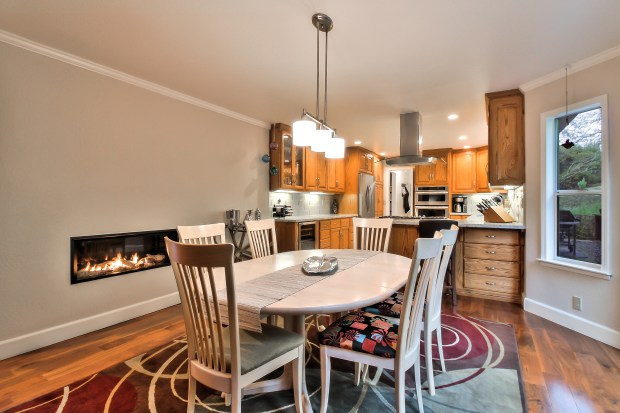 At the Sycamore Drive home, the kitchen is well-appointed and a stylish linear fireplace warms the casual dining area.