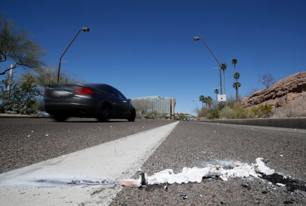 A vehicle goes by the scene of Sunday's fatality where a pedestrian was stuck by an Uber vehicle in autonomous mode, in Tempe, Ariz., Monday, March 19, 2018. A self-driving Uber SUV struck and killed the woman in suburban Phoenix in the first death involving a fully autonomous test vehicle. (AP Photo/Chris Carlson)