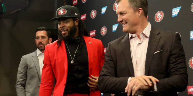 Richard Sherman, wearing a bright red suit, takes the stage with San Francisco 49ers head coach Kyle Shanahan and general manager John Lynch, Tuesday, March 20, 2018, at the San Francisco 49ers headquarters in Santa Clara, Calif. Sherman recently signed a contract to play with San Francisco. (Karl Mondon/Bay Area News Group)